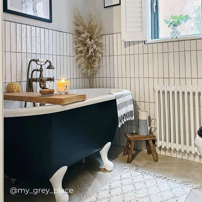 white column radiator next to a roll top bath