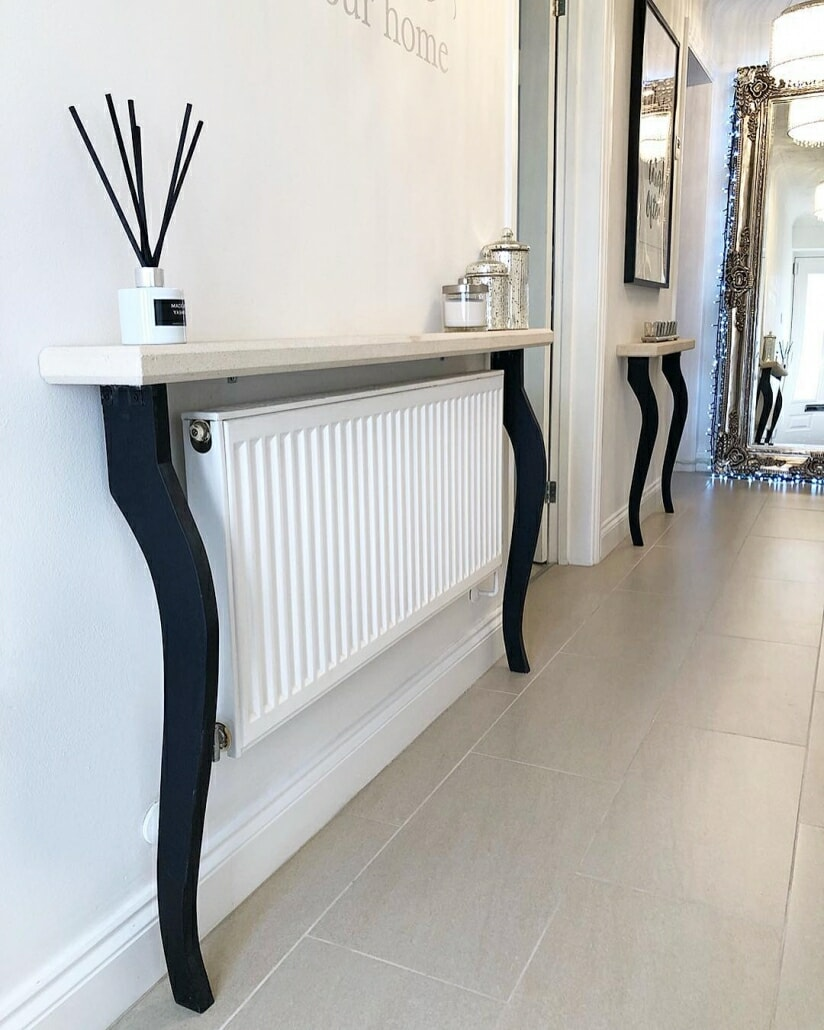 A white convector radiator on a white wall under a shelf.