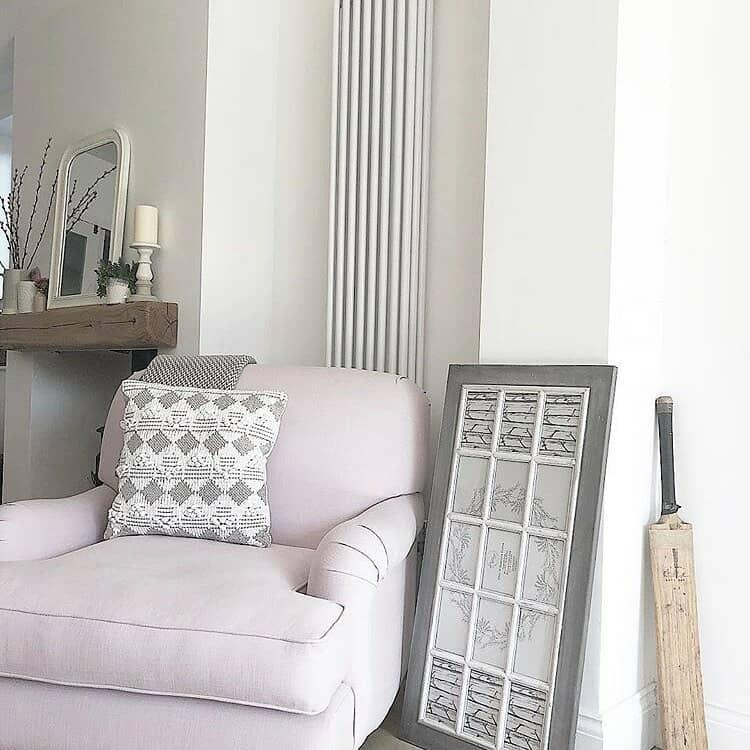 white vertical column radiator behing a pink armchair