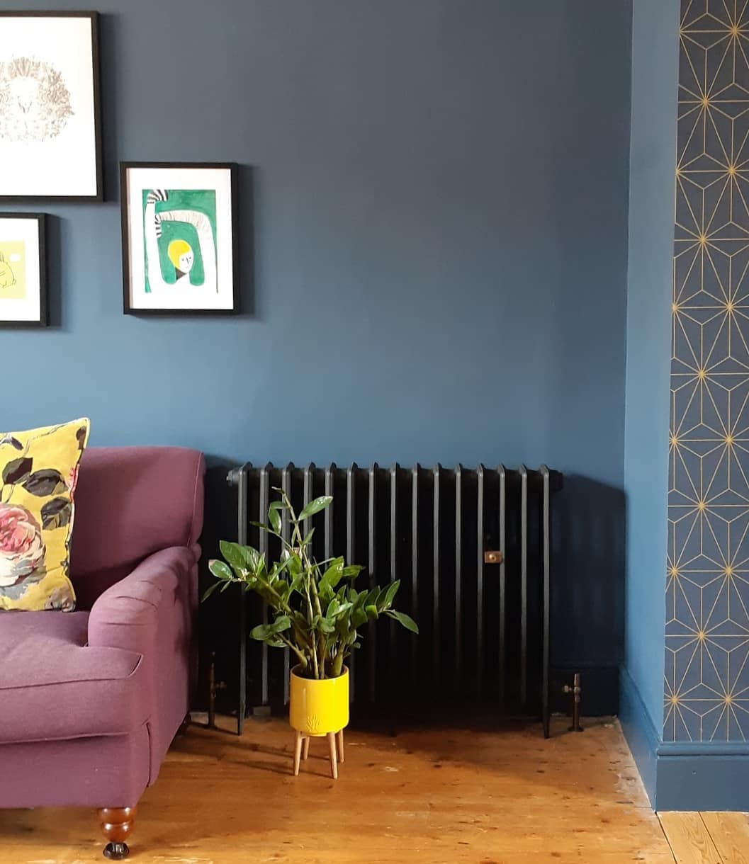 A black cast-iron radiator on a navy wall.
