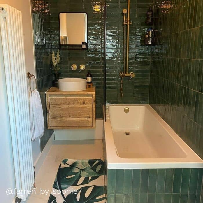 white vertical radiator in a green bathroom