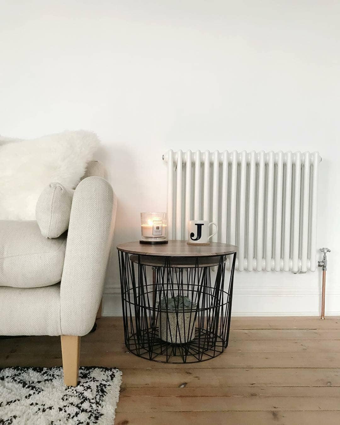 white column radiator next to a cream sofa