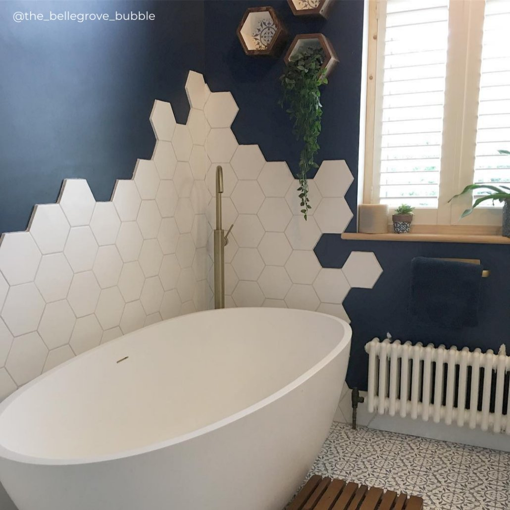 low level white column radiator in a blue bathroom