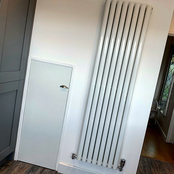 white vertical radiator on a white wall