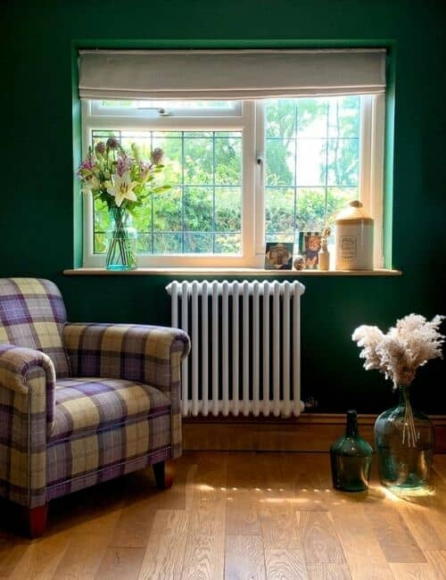 white column radiator on a green wall