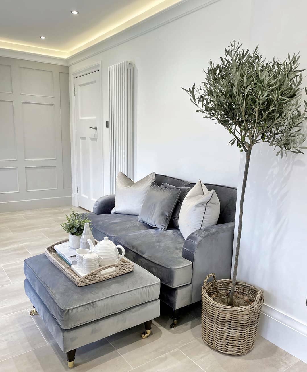 white vertical radiator behind a grey sofa