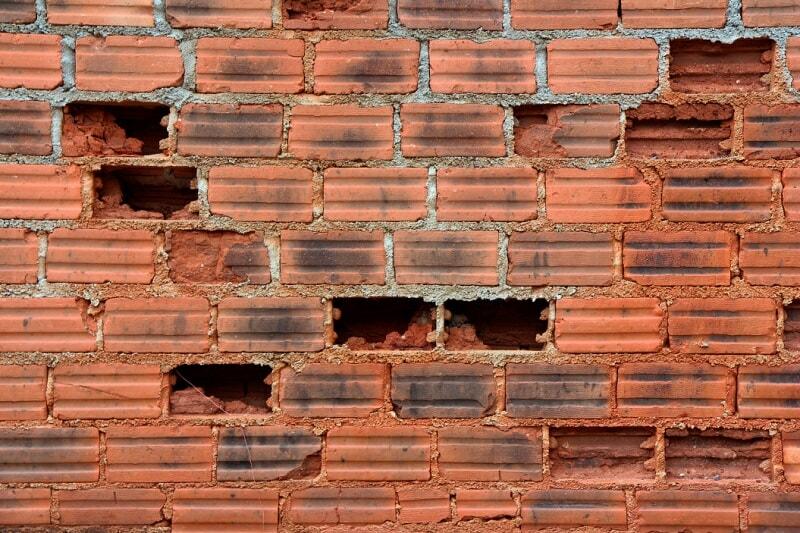 a broken brick wall with missing bricks