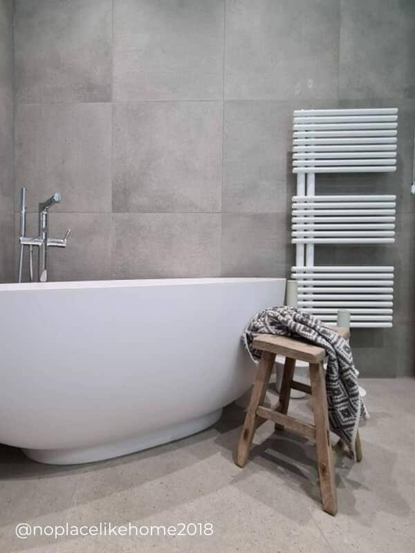 modern white heated towel rail in a minimal bathroom