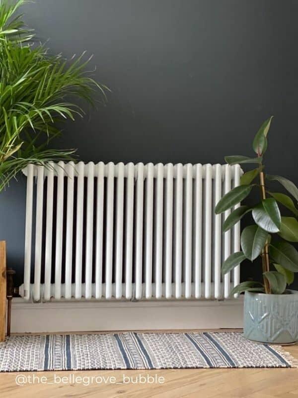 a white horizontal radiator on a blue wall