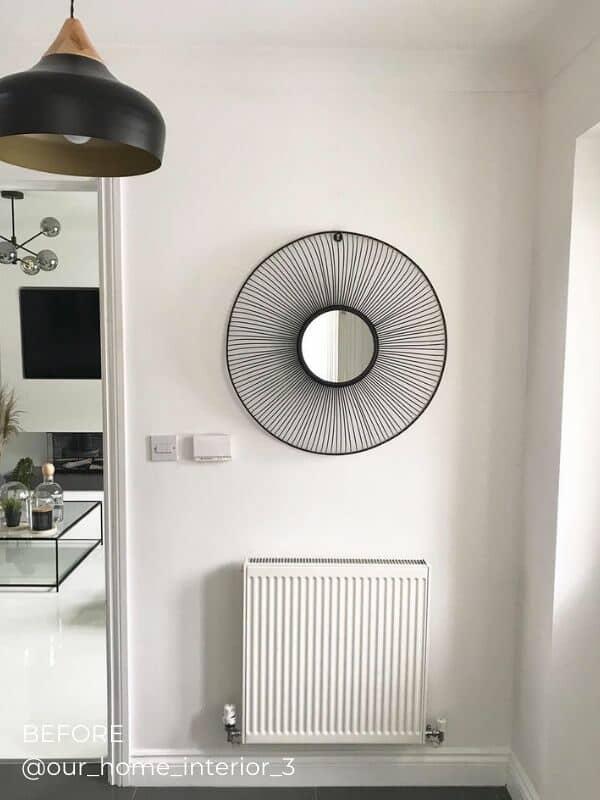 a standard white horizontal radiator in a hallway