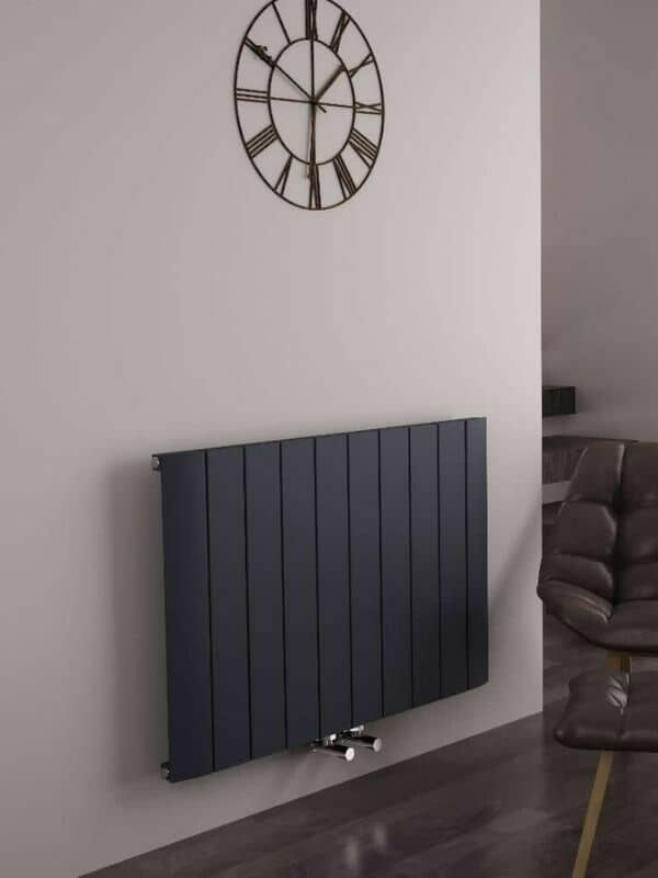 a modern anthracite horizontal radiator on a grey wall