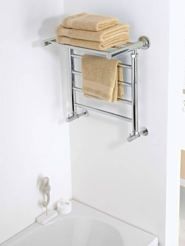 shelf style heated towel rail in a bathroom with towels