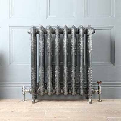 A metallic cast iron radiator against a grey panelled wall