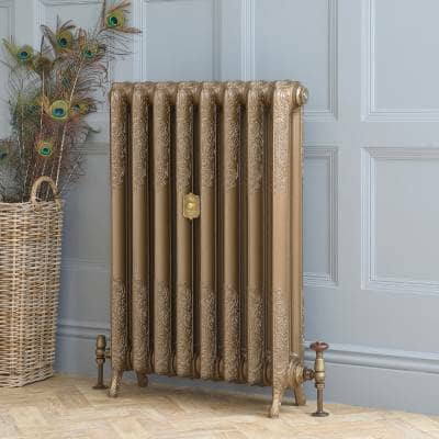 gold cast iron central heating radiator in front of a blue wall