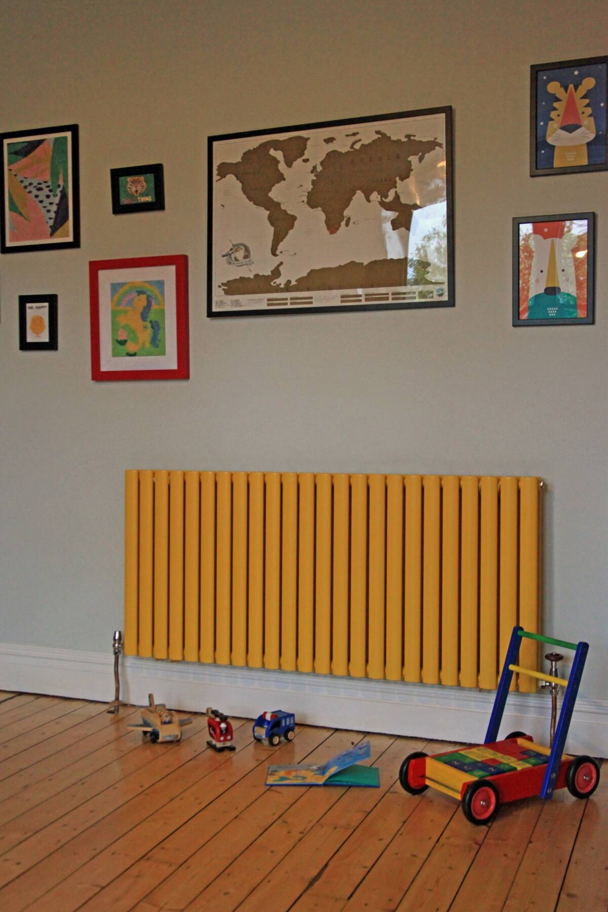 yellow radiator in a playroom with toys on the floor
