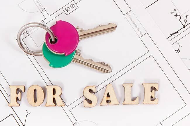 A set of house keys with a for sale sign