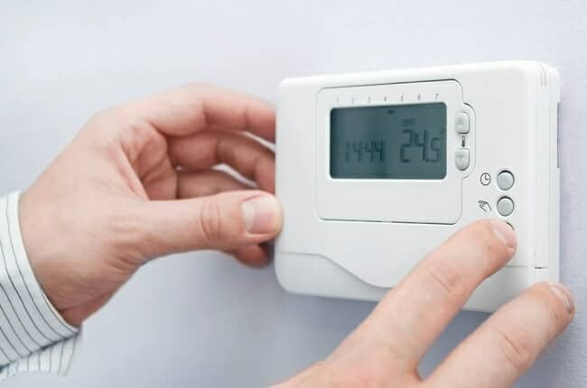 A man turning on a heating thermostat