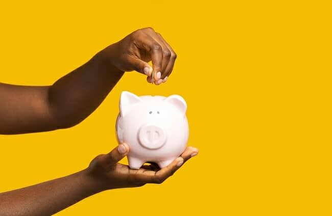 A black woman putting money in a piggy bank