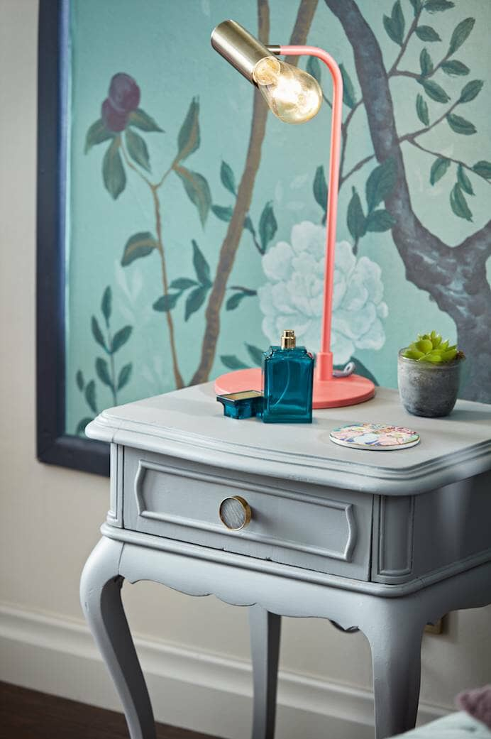 vintage side table in front of a mural wall