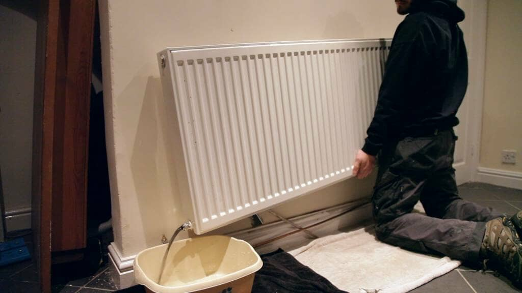 A man tipping a domestic radiator to remove water from the inside