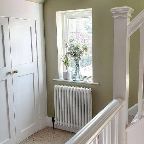 triple column white radiator under a window