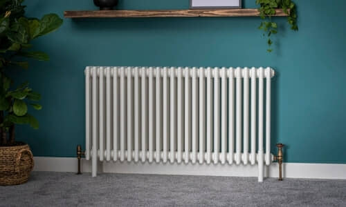 traditional white column radiator on a blue wall