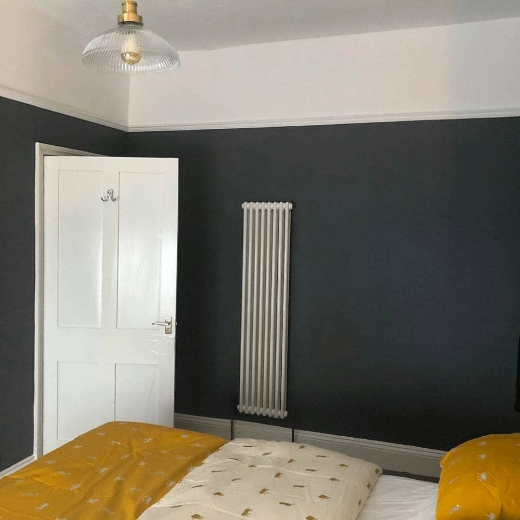 Milano Windsor white vertical radiator on a navy wall