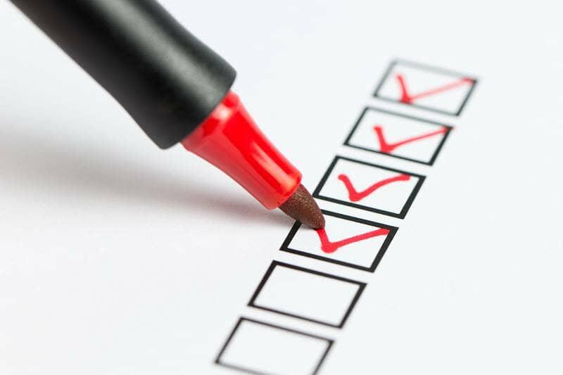 a red pen checking a box on a checklist
