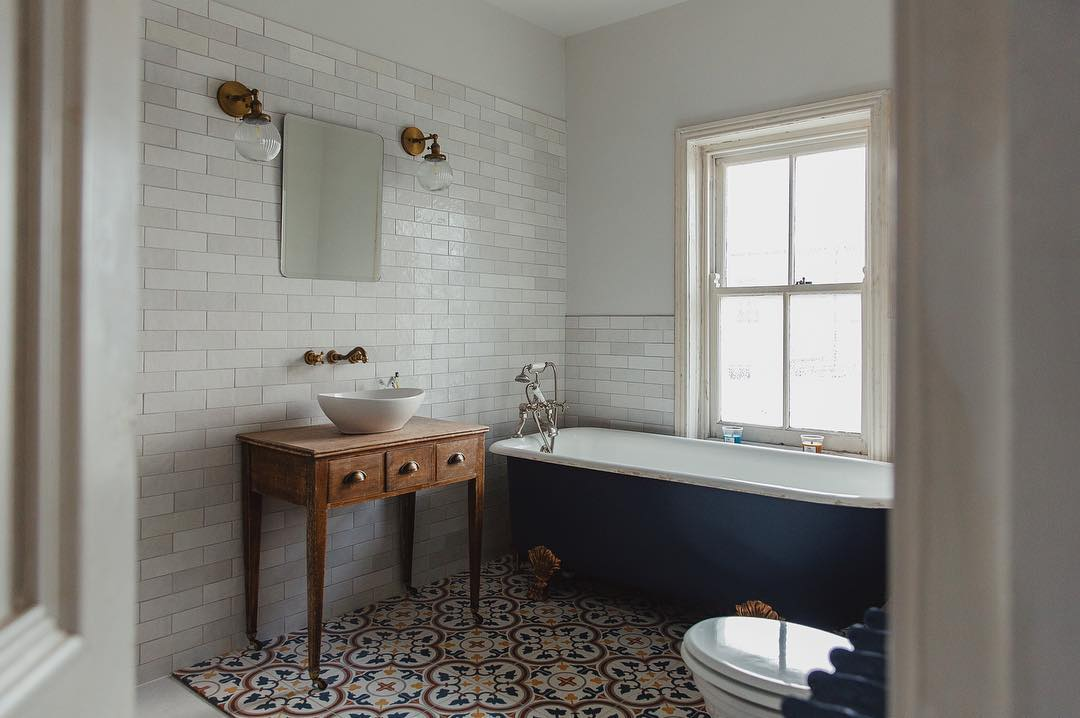 A blue freestanding bath in a white bathroom under a window.