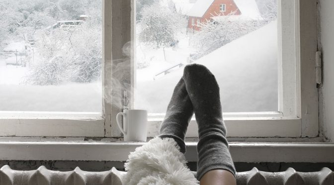 A woman's feet raised up on to a radiator with snow visible through a window