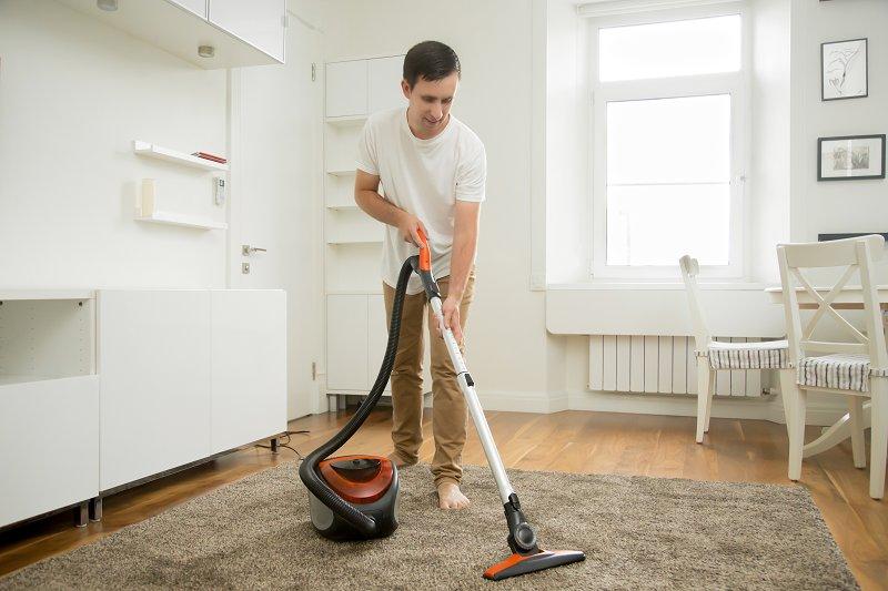 happy man vacuuming