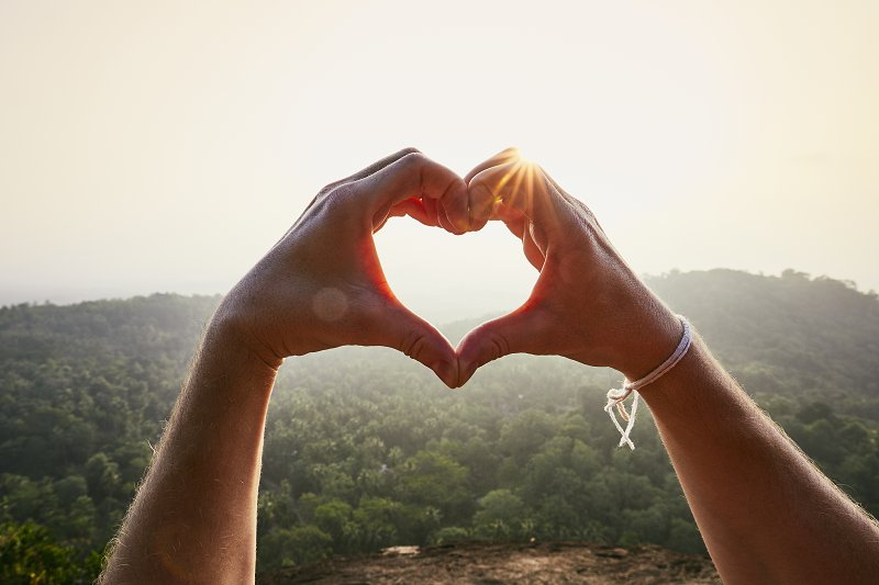 heart shape made with hands against a sunset