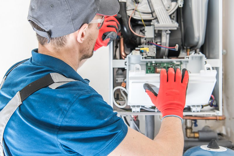 a man working on a gas cdentral heating boiler