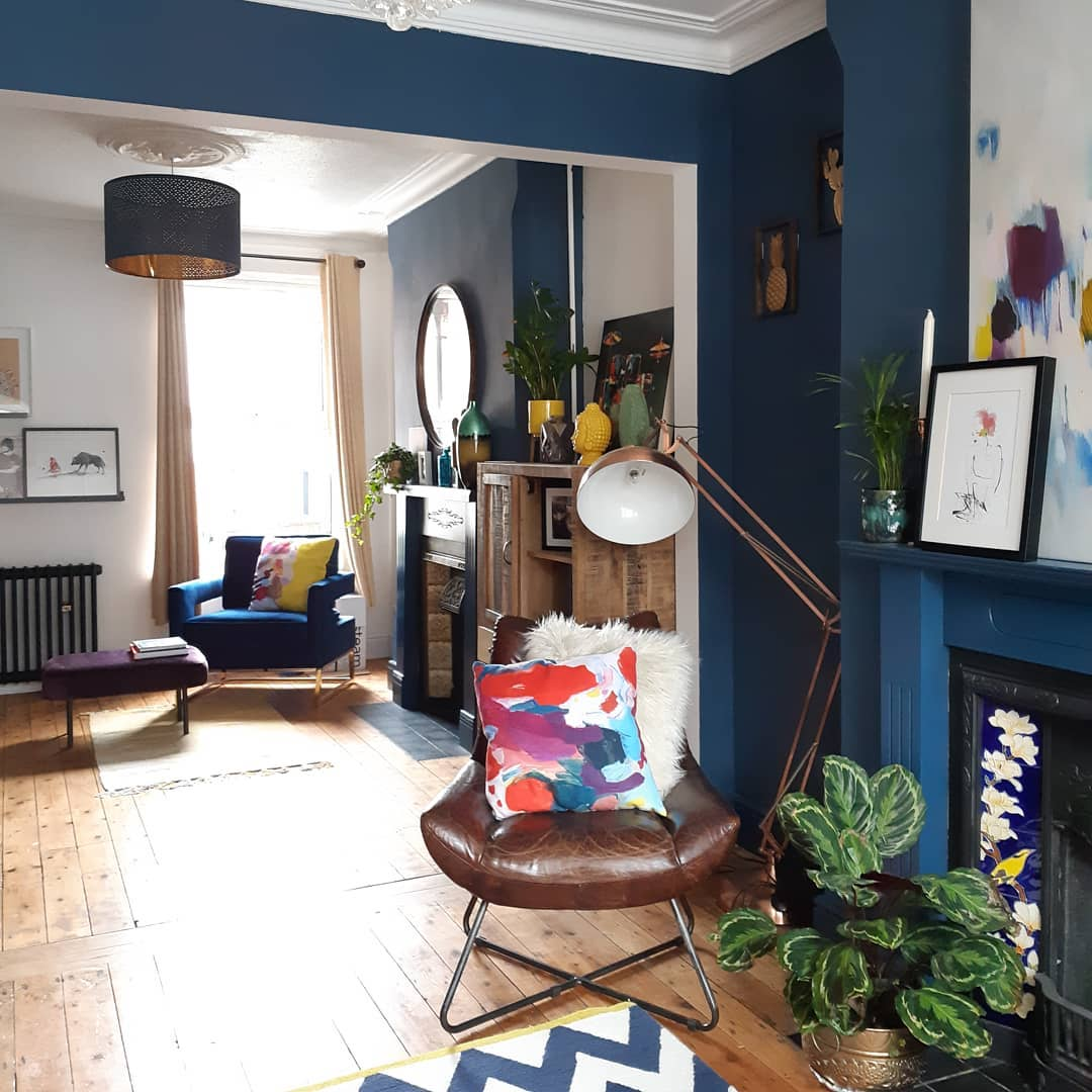 A colourful living room with wooden flooring and a cast-iron radiator.