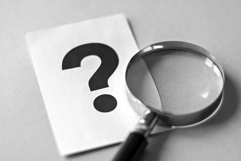 magnifying glass and question mark on paper