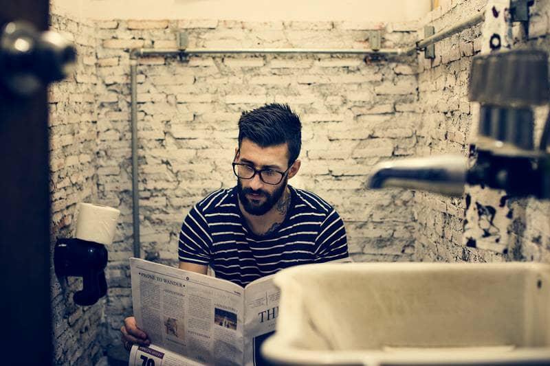man-in-a-restroom-reading-newspaper