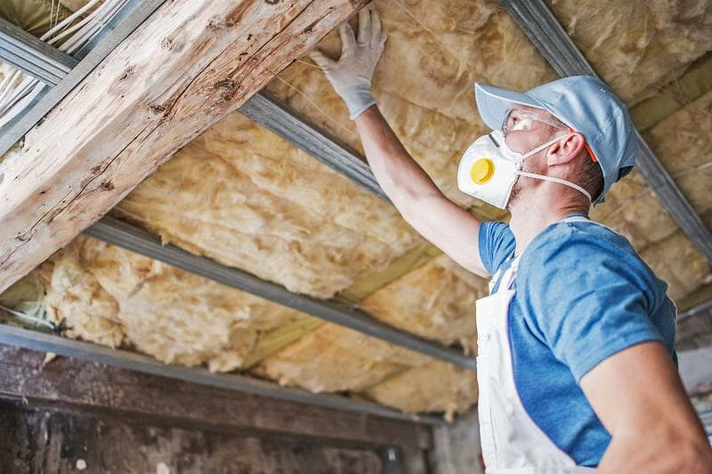 a workman inspecting roof insulation