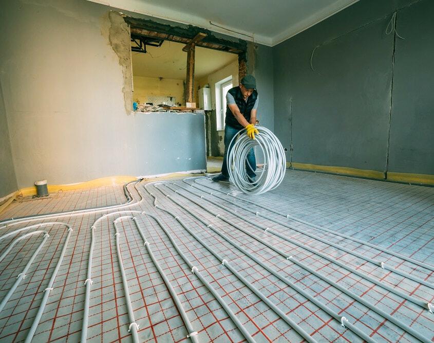Pipefitter installing underfloor heating pipes