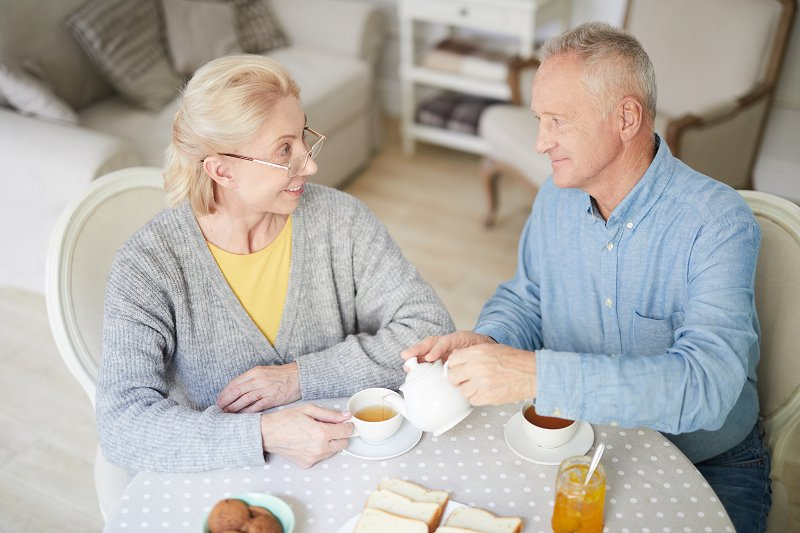 An elderly couple having a cup of tea and smiling at each other