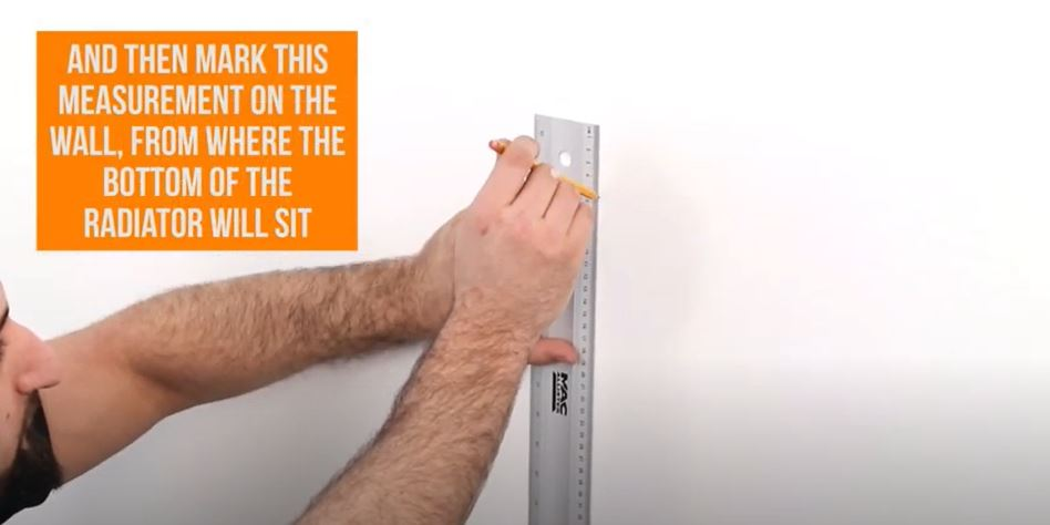 hand marking a line on a wall with a ruler