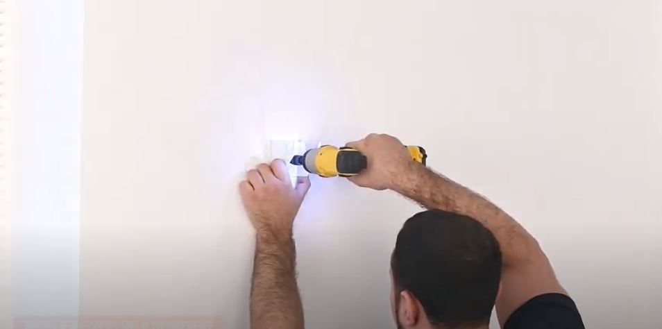 man fixing radiator brackets to a wall with a drill