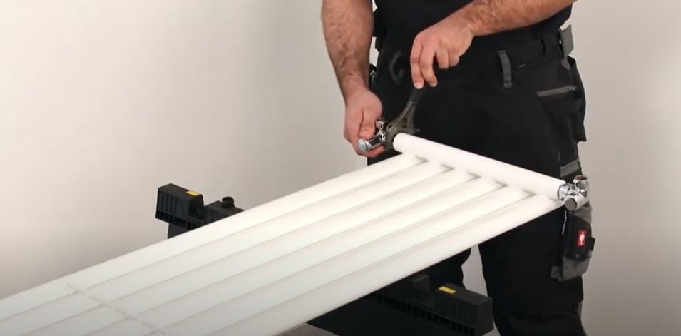 man inserting radiator valves to a vertical radiator