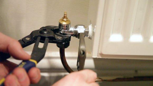 A man removing a radiator valve form a radiator