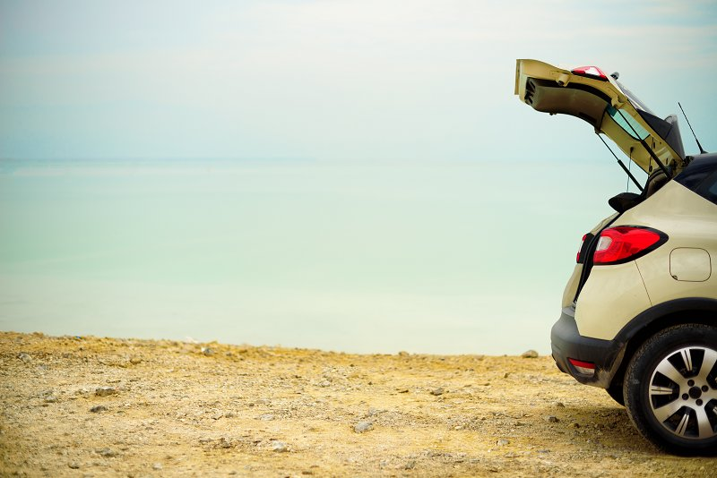 a car with its boot open at the beach