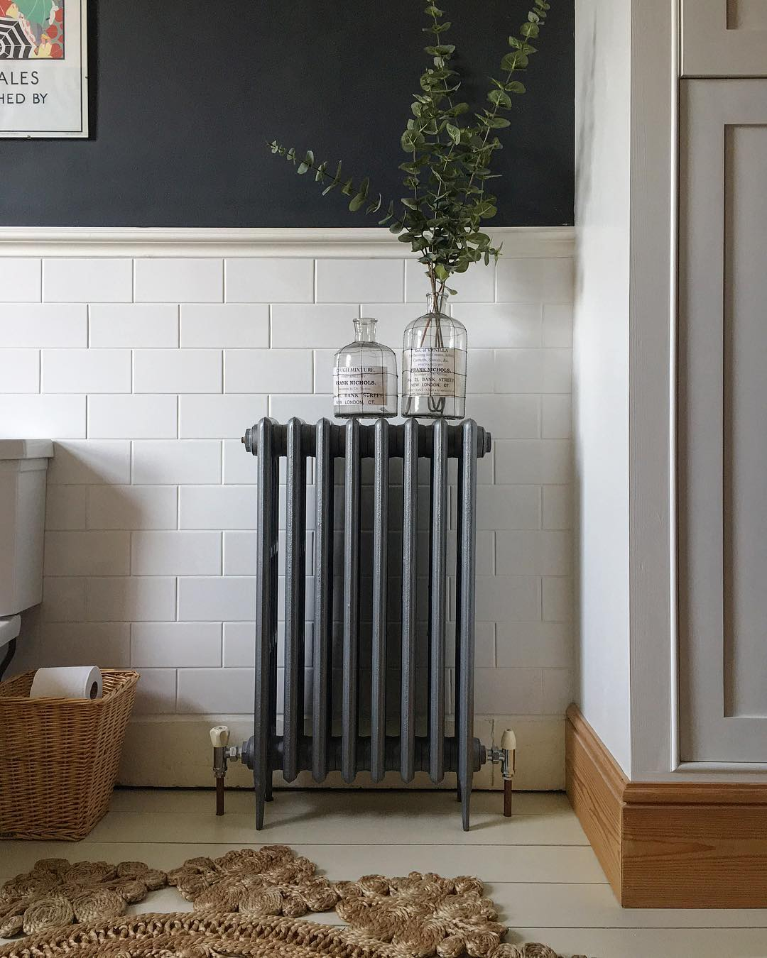 A grey cast-iron radiator on a white wall.